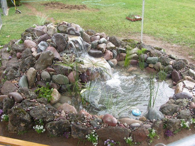 A small pond (5'x7') with one sheer waterfall then cascading down more boulders.